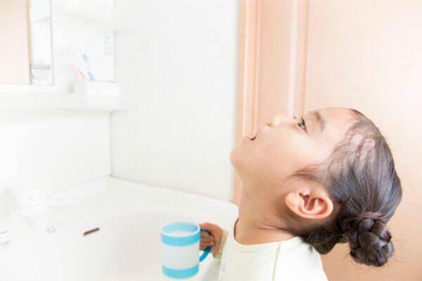 インフルエンザ予防のためにうがいをする小学生の女の子